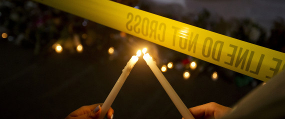 Olina Ortega, left, and Austin Gibbs light candles at a sidewalk memorial in front of Emanuel AME Church where people were killed by a white gunman Wednesday during a prayer meeting inside the historic black church in Charleston, S.C., Thursday, June 18, 2015. (AP Photo/David Goldman)
